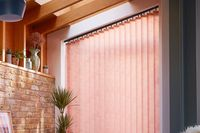 peach coloured vertical blinds fitted on a wide window in a living room with exposed brick work and wood slats