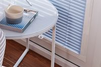 A close up image of pleated conservatory blinds fitted to a window which is next to a side table