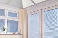 Blue coloured vertical blinds fitted to a tall and wide window in a bathroom that is decorated in white