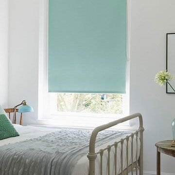 Light blue roller blind fitted to a rectangular window in a bedroom decorated in white