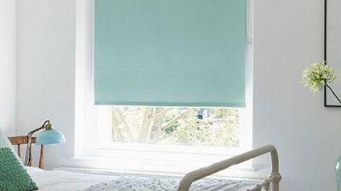 Blue coloured roller blind fitted to a tall rectangular window in a bedroom that has white walls