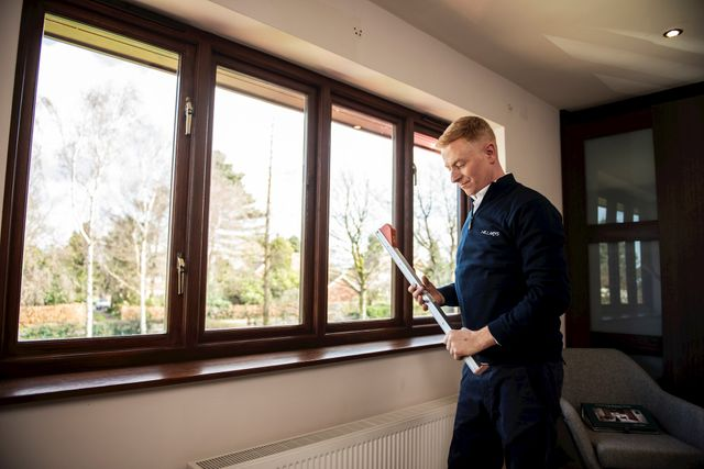 An advisor measuring for blinds across a series of four wooden blinds