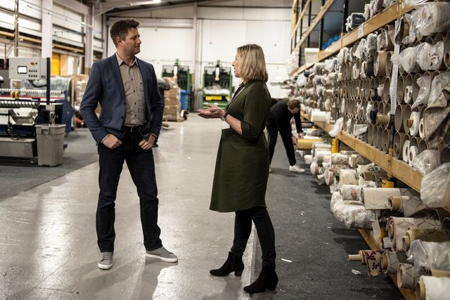 Somebody talking to a member of the product team in a hillarys warehouse which has rolls of fabric stacked onto the shelves