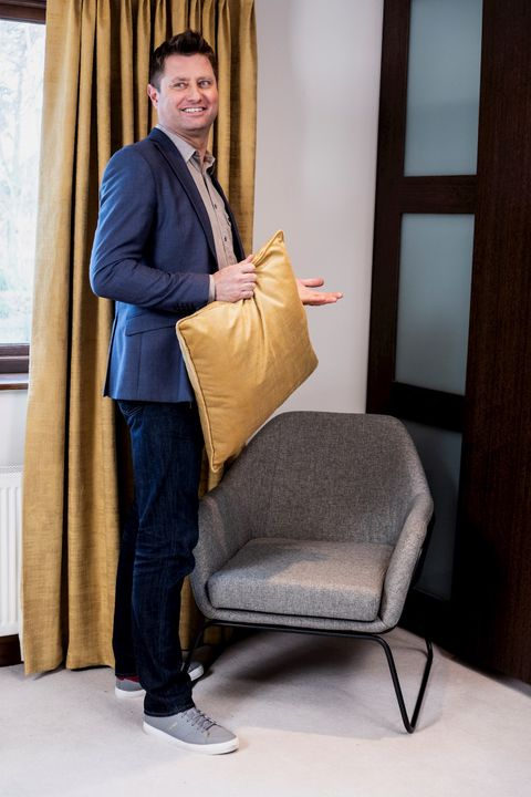 George Clarke with customers curtains and holding yellow cushion