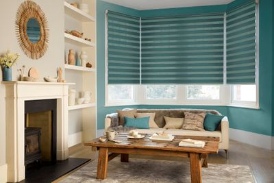 Teal coloured day and night blinds fitted to a bay window in a living room decorated in blue and cream colours while also featuring a sofa, coffee table and fireplace