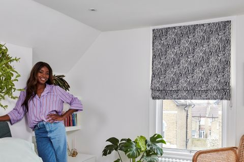 AJ Odudu in a white decorated bedroom with a grey and white patterned roman blind fitted to a rectangular window