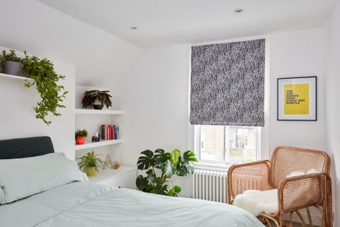 blue and white Roman blind in bedroom window with many plants and a wicker chair