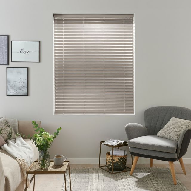 pale washed out grey wooden Venetian blind with frames on the wall and grey arm chair with wooden legs