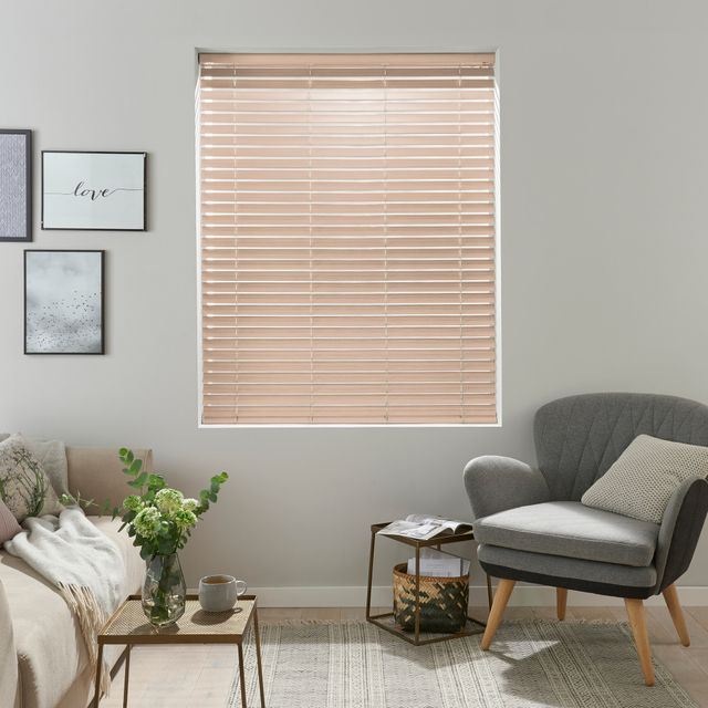 light wooden Venetian blind with frames on the wall and grey arm chair with wooden legs
