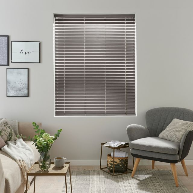 grey wooden Venetian blind with frames on the wall and grey arm chair with wooden legs