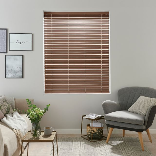 rich walnut brown wooden Venetian blind with frames on the wall and grey arm chair with wooden legs