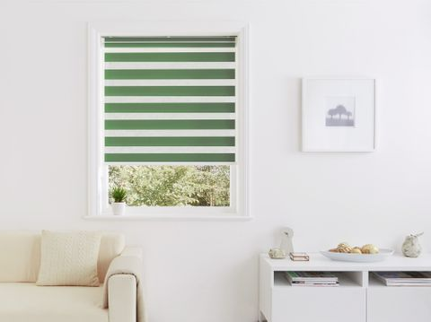 green striped Day and Night blind in small window with cream sofa