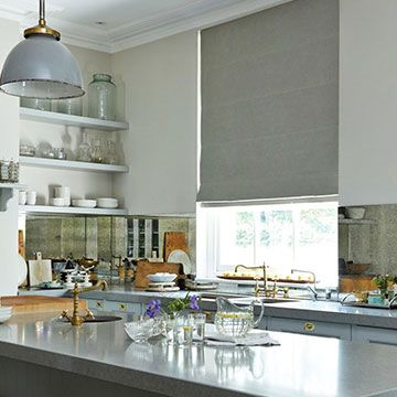 Grey coloured roman blind is fitted to a tall rectangular window in a kitchen with grey countertops, white walls and a range of kitchenware