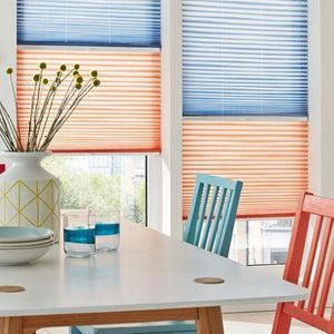 A tall white window has two pleated blinds fitted to the frame with the top blind in blue and the bottom blind in red they are in a dining room decorated in white that has two dining chairs in red and blue