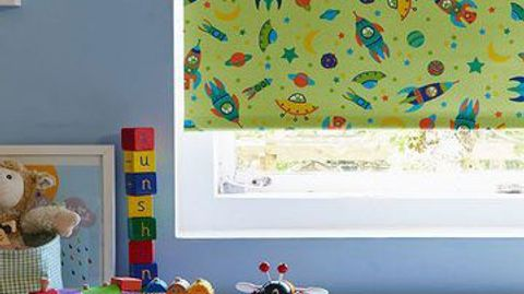 Green coloured roller blind with space ships, planets and space objects in various colours that has been fitted to a rectangular window in a kids room which has toys on the floor
