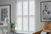 An image of white coloured tier shutters in a room with white coloured walls