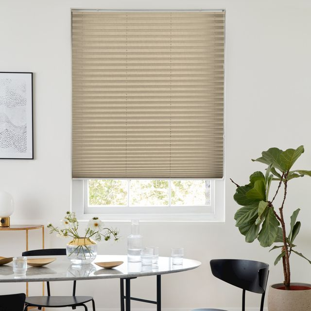 Caramel coloured pleated blinds fitted to a rectangular window in a modern dining room setting that has white decorated walls