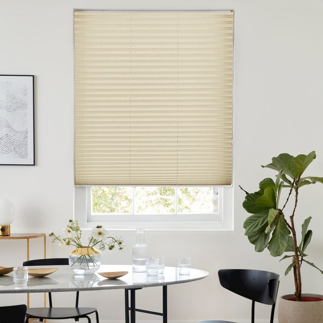 A pleated blind designed with a sandstone colour against white walls and fitted to a large rectangular window in a dining room