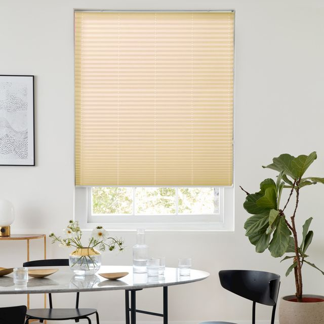 A pleated blind that is beige in colour and fitted to a rectangular window in the middle of a modern looking dining room that has white decorated walls