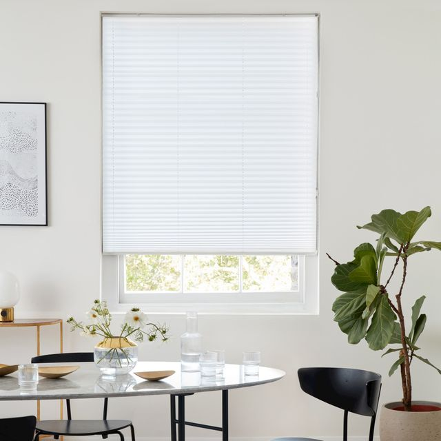 White coloured Pleated blinds fitted to a rectangular shaped window while the dining room is decorated with modern ornaments and white walls