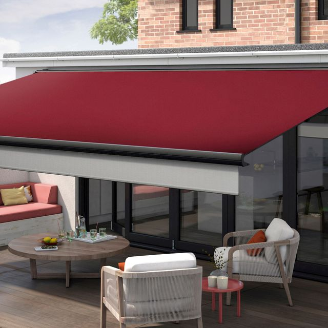 Dark Red Rouge Awnings above glass doors in a garden. The Awning is fully extended to provide shade for the comfortable outside seating area.