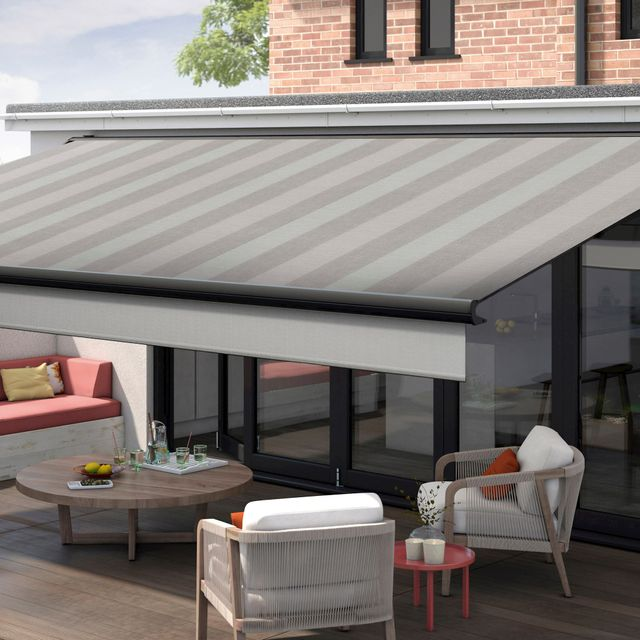 Outisde seating area fitted with Pencil Grey in a striped Silver pattern. The Awning is fully extended, providing shade for the seating area of wicker patio furniture and a sleek circular wooden table.