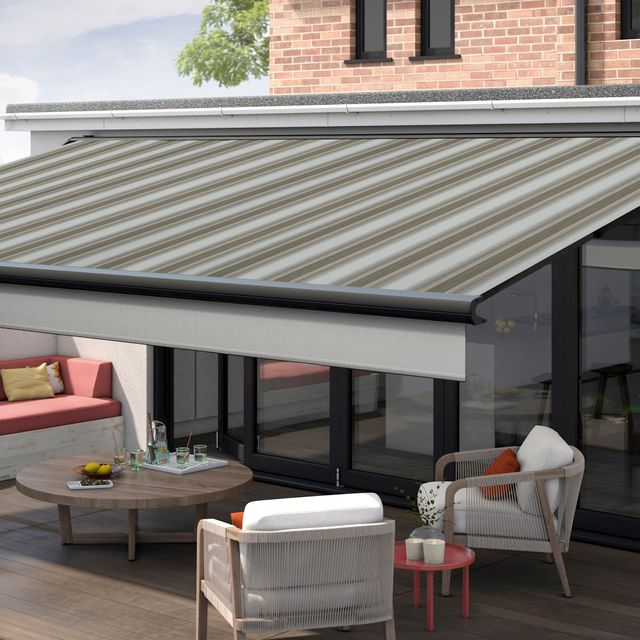 Awning on a ground level home extension. The Awning is finished in the Baden Baden fabric and is above an outdoor patio area, decorated with wicker patio furniture and a circular wooden table.