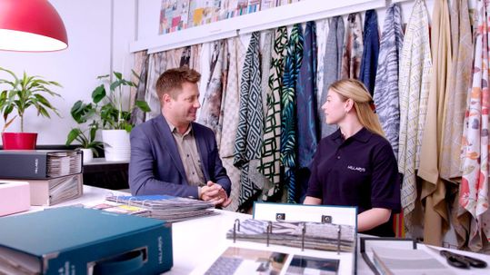 George Clarke sits with female advisor with vibrant fabrics hanging behind them and books of fabric swatches on the table