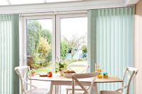 Green coloured vertical conservatory blinds fitted to large windows in a conservatory