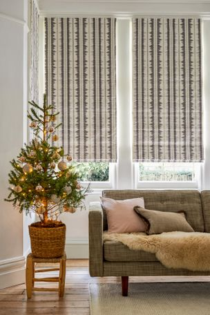 An image of a roman blind in the vivado ash style which has been fitted to three large windows in a living room that is decorated with white walls, a sofa and a small christmas tree