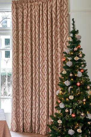an image of floor to ceiling curtains decorating a home next to a christmas tree