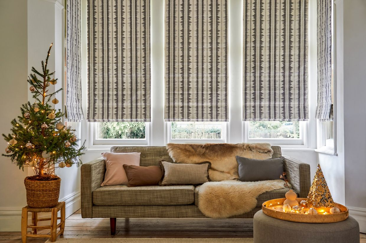 Cream and grey striped Roman blinds in a window behind a sofa and Christmas tree with gold lights and decorations