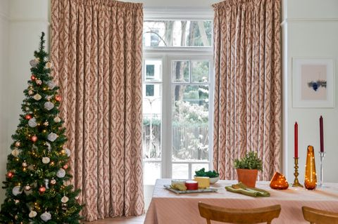 Pink Aztec patterned curtains in a bay window behind a table decorated with Christmas candles and lights and a Christmas tree with rose gold decorations