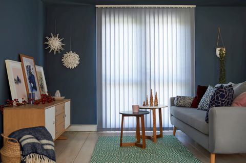 A lounge with navy walls, a grey sofa and pale blue vertical blinds in the french door, some wooden and paper Christmas decorations are around the room