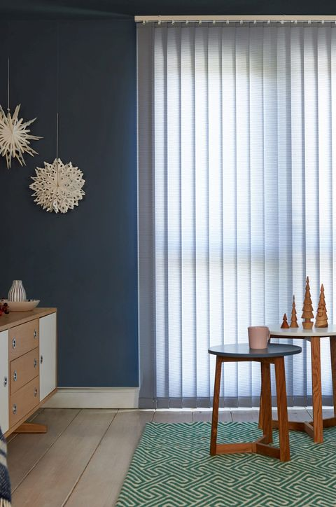 Pale blue vertical blinds cover a large french door, a navy wall and funky green rug and a table with wooden Christmas decorations on it