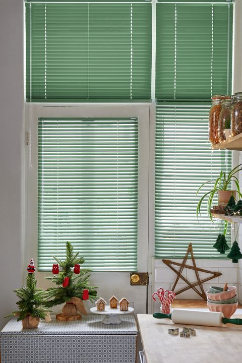 Green metal venetian blinds are half closed in a kitchen with Christmas decorations and baking equipment