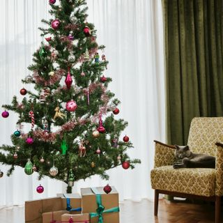 Green full length curtains matched with white net curtains in a living room with a fully decorated christmas tree in the middle of the room surrounded by presents while a cat sits on a yellow armchair