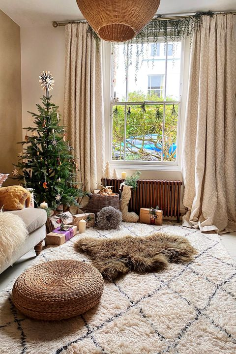 Christmas tree sat infront of a window in a neutral living room with neutral curtains draped to the floor