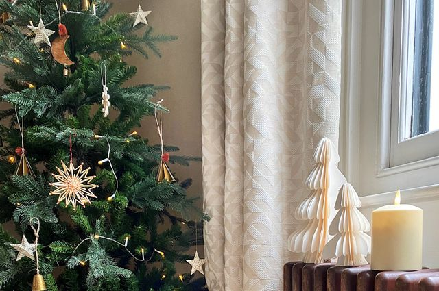 Close up of Christmas tree next to window with neutral curtains and Christmas decorations on the window sill