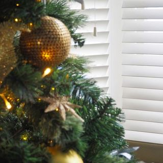 Beautiful Christmas tree decorated with gold baubles and lights infront of white wooden vertical blinds