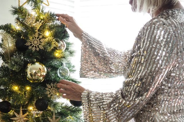 Close up of lady putting decorations on a beautiful Christmas tree decorated with gold baubles and lights infront of white wooden venetian blinds