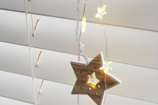 Close up of wooden star decoration fairy lights draped down a white wood venetian blind