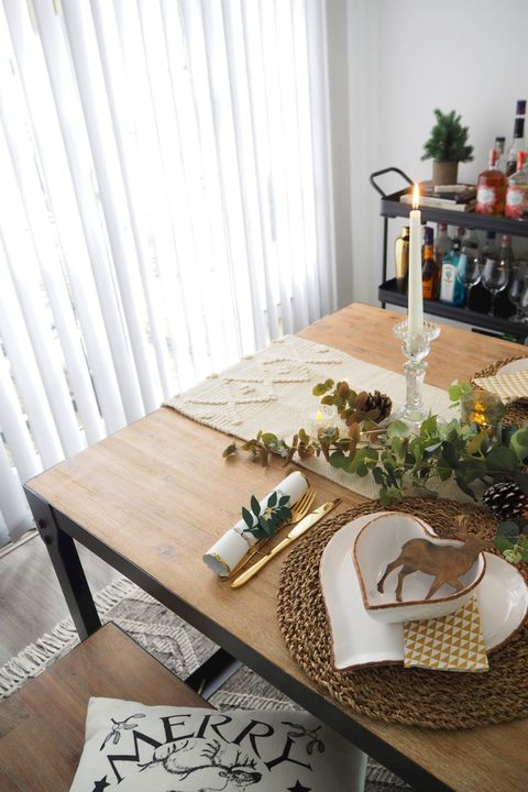 Christmas dining table place set with gold coloured cutlery, candles and foliage, white vertical blinds in the background