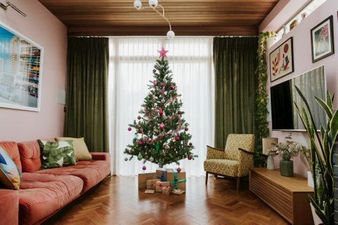 Luxe green curtains and soft white voiles layered in a large window in a room with retro decor and a Christmas tree