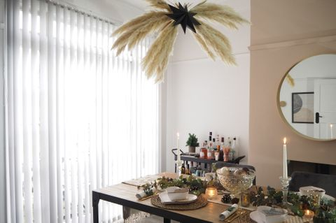 Dining table decorated for Christmas with pampas grass decoration over head and white vertical blinds in the window