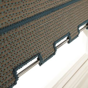 close up detailed shot of the shaped hem on a roller blind with delicate blue details around the hem