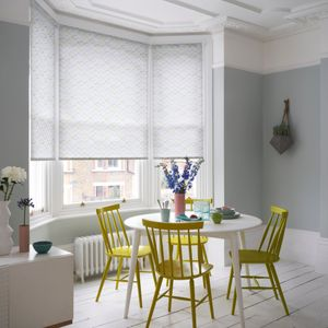 white roller blinds with bright details in a bay window in a dining room with funky bright yellow dining chairs