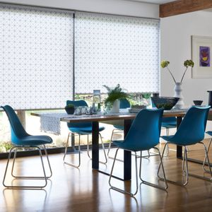 Cosmic Jet white and blue roller blinds in a wide window behind a dining table with blue chairs