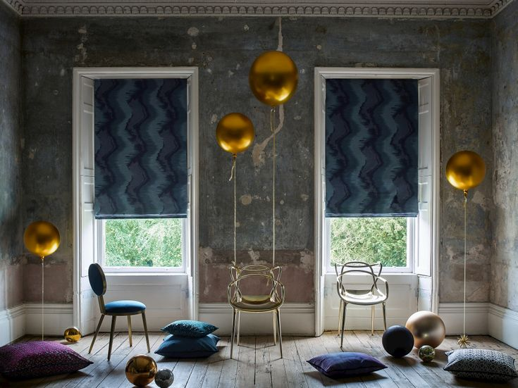 Dark blue swirled Roman blinds sit in 2 windows in a room with blue and purple cushions and gold balloons