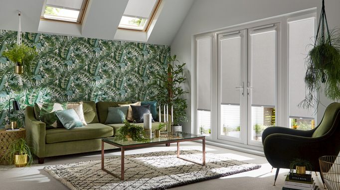 Perfect fit acacia silver roller blinds against patio doors in planted themed living room with green furniture and